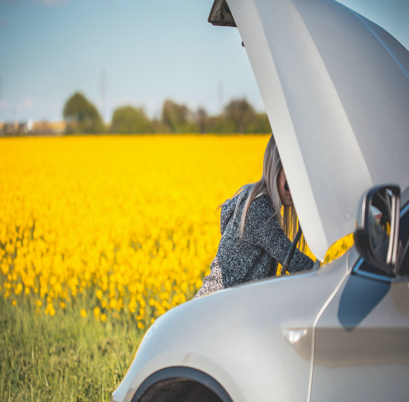 young-woman-trying-to-check-and-repair-her-broken-car-picjumbo-com 2350 2309